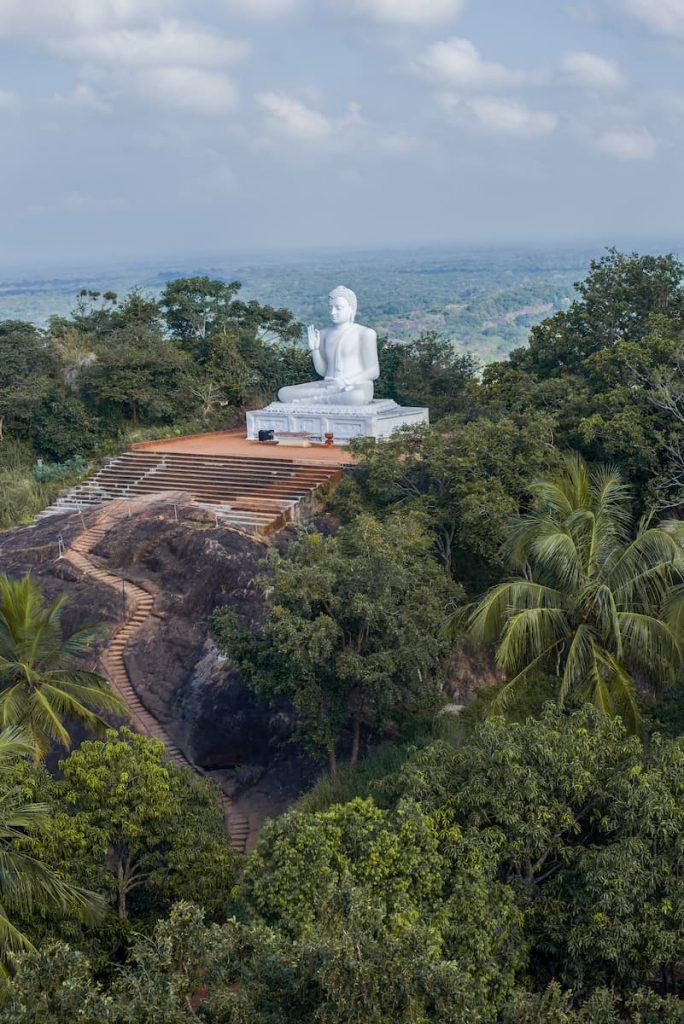 Vue de la sculpture blanche du Bouddha assis sur le plateau d'Ambastala (plateau de la mangue) par une journée nuageuse. Mihintale, Sri Lanka